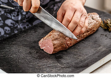 Chef is cutting meat