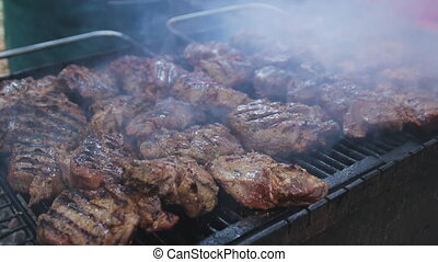 Chef is flipping meat on grill. Barbecue meat preparing on...
