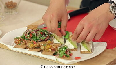 Chef is Making Bruschettas with Vegetable Mix, Pears and Nuts