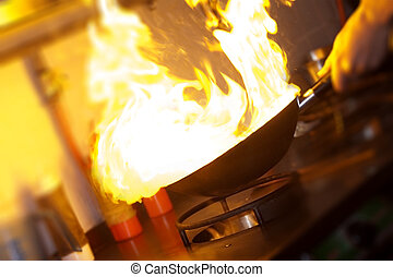 Chef is making flambe with pan and fire