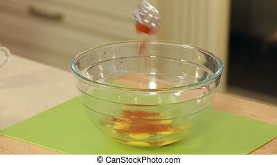 Chef is Mixing Salt and Spices with Chicken Eggs in a Glass Bowl