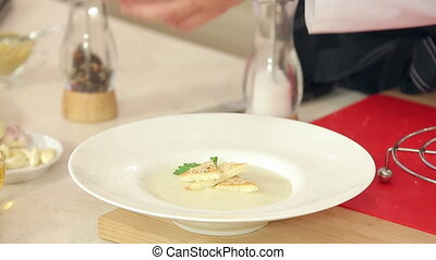 Chef is Putting Dill, Parsley, Salt and Pepper in a Plate with Cream Soup, Crispy Toasts and Grated Cheese