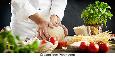 Chef kneading raw dough for an Italian pizza