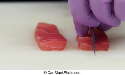 Chef lays out thin slices of fish. Close up - Chef lays out...