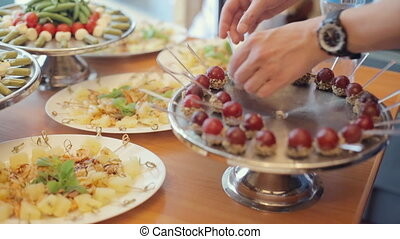 Chef lays ripe grapes in the nuts and chocolate on a large silver tray