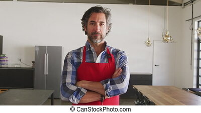 Portrait of a senior Caucasian man with a beard, wearing a red apron and a checked shirt, standing in cookery class with arms crossed, looking to camera and smiling, in slow motion