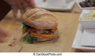 Chef makes sandwich. Handheld shot