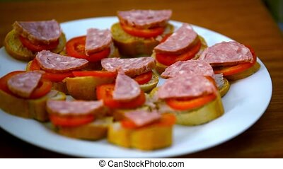 Chef makes sandwiches with pate, tomatoes, sausage and...