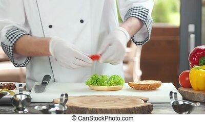 Chef making a healthy burger. Bun and fresh vegetables.