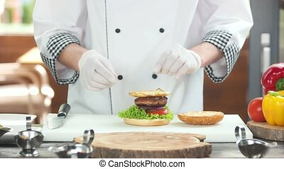 Chef making burger. Bun, meat and cheese.