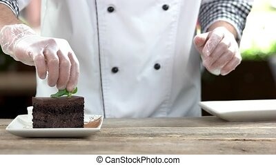 Chef making dessert. Belgian chocolate cake, mint.