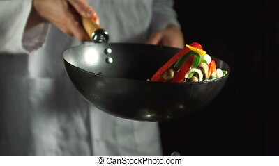 Chef making vegetable stir fry in wok in slow motion