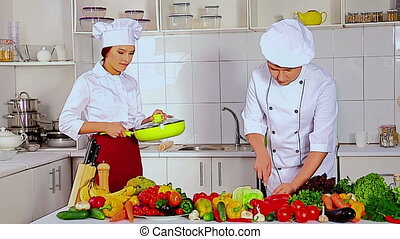 Chef man and woman professional in hat cooking vagetable . Used tripot.