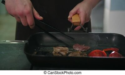 Chef on kitchen is frying meat and vegetables in a pan,...