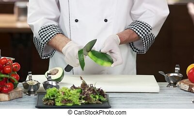Chef peeling avocado. Food preparation, tropical fruit.