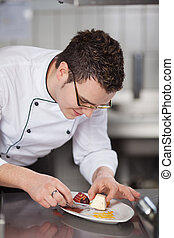 Young male chef placing ice cream in garnished plate at commercial kitchen counter