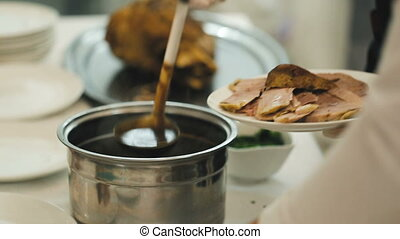 Chef Pouring Dark Sauce on Baked Lamb Meat