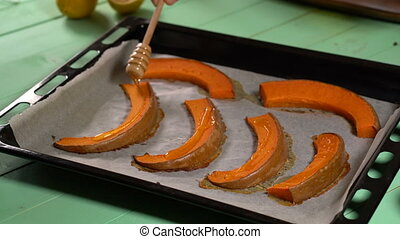 Chef pours honey on the baked pumpkin slices, close up