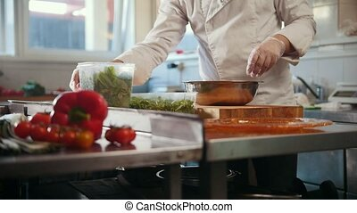 Chef prepares a salad by adding herbs and spices, vegetables...
