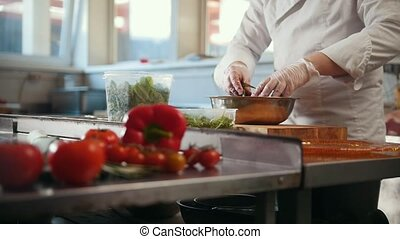 Chef prepares a salad by mixing the ingredients by hands, vegetables in the foreground