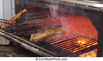 Chef prepares beef steak slow motion HD video: flips meat in grill charcoal oven. Cooking process on barbecue restaurant kitchen
