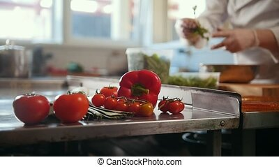 Chef preparing a salad in the kitchen of the restaurant,...