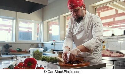 Chef preparing a salad mixing the ingredients in the kitchen of the restaurant