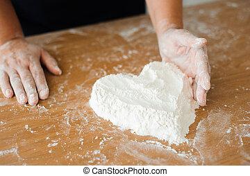 Chef preparing dough - cooking process, flour heart.