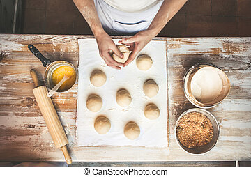 Chef preparing dough in a kitchen.