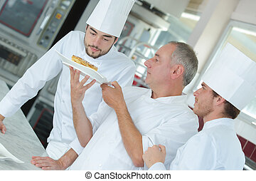 chef preparing food in the kitchen with apprentices