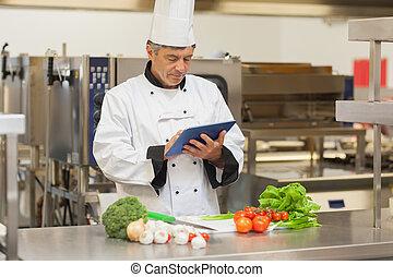 Chef preparing recipe with digital tablet