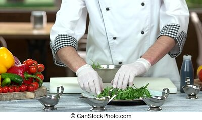 Chef preparing salad, herb.