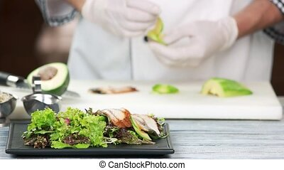 Chef preparing salad with eel. Lettuce, avocado and fish.