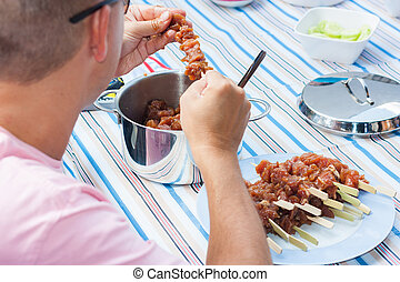 Chef sitting at a picnic table and preparing marinated pork and chicken skewers for the grill BBQ
