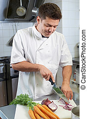 Chef Preparing Vegetables In Restaurant Kitchen