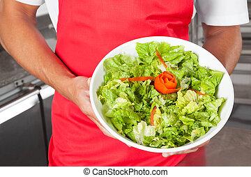 Chef Presenting Salad In Kitchen