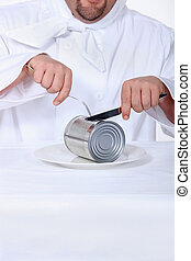 Chef pretending to cut tin can with knife and fork
