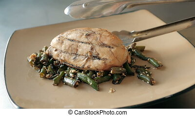 chef puts a piece of roast meat on green beans on a plate in a restaurant. concept of cooking dishes step by step