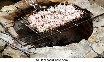 Chef puts meat on the fire, barbecue. Chef measures...