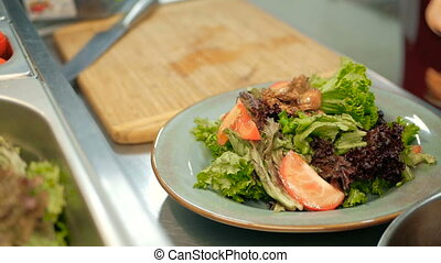 chef puts pieces of fried liver on a salad in a restaurant kitchen. cooking salad step by step