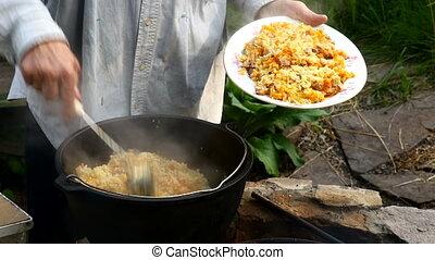 Chef puts the original Uzbek pilaf in a bowl. Cooking Uzbek...
