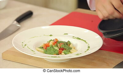 Chef Putting Fried Red Cherry Tomatoes on Pasta with Green Pesto in a Plate