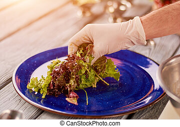 Chef putting green salad on porcelain plate.
