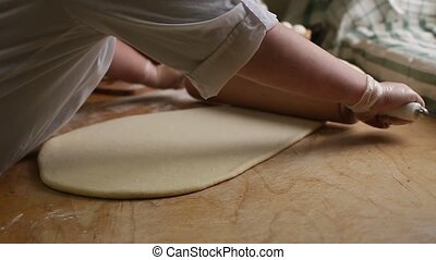 Chef rolling dough with rolling pin - Woman baker rolls the...