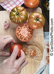 Chef rubbing tomato on a slice of bread