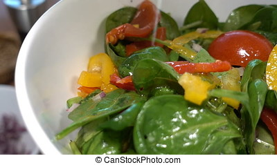 Chef seasoning a spinach salad with colorful bell pepper and red onion, zoom out