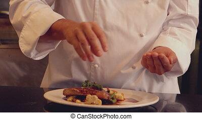Chef seasoning dish in slow motion