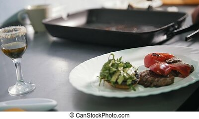 Chef serves steak on the plate in restaurant, close-up view