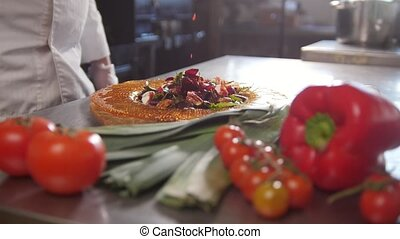 Chef serves the salad by placing the components on a plate and adding the sauce, fresh vegetables in the foreground