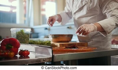 Chef serves the salad by placing the ingredients on a plate,...